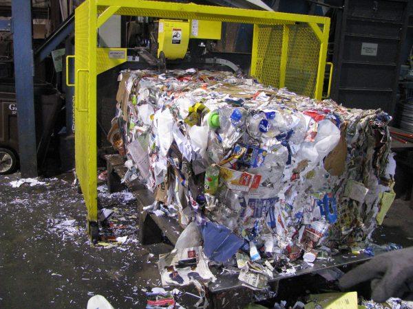 The mechanic baler pushes out a brick of single-stream recyclables.