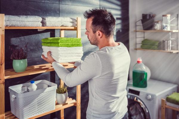 Men arranging clean towels at laundry room