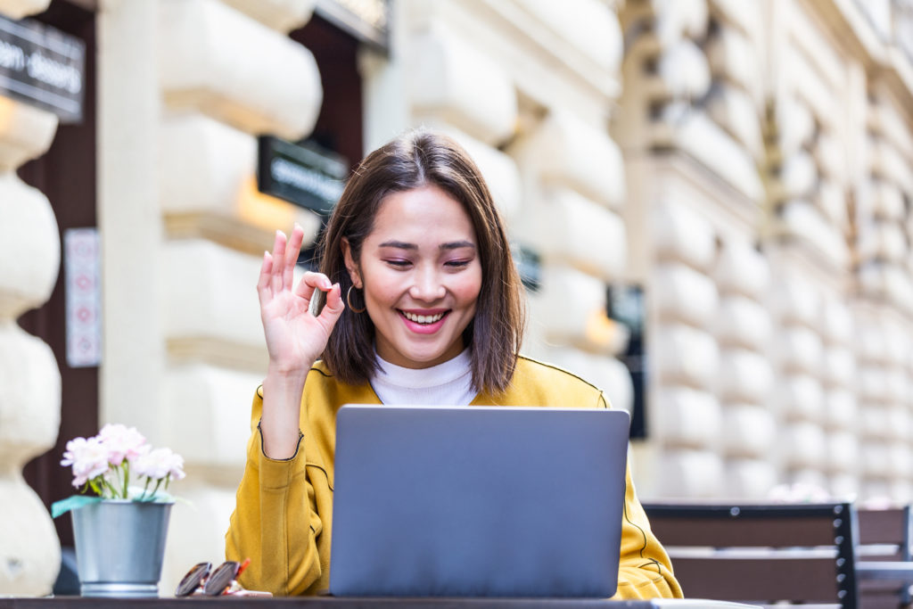 Beautiful Asian woman sitting with portable net-book laptop in modern cafe bar video chatting, young charming asian female freelancer thinking about new ideas during work on laptop computer